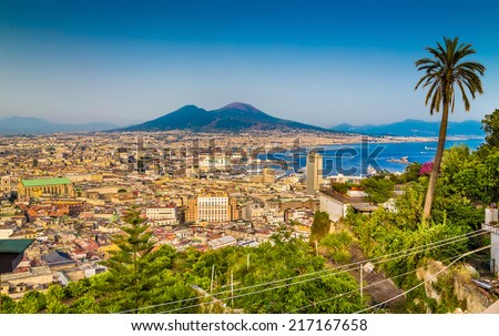 Scenic picture-postcard view of the city of Napoli (Naples) with famous Mount Vesuvius in the background in golden evening light at sunset, Campania, Italy - stock photo