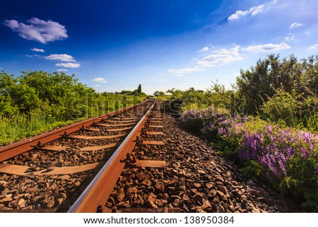 Scenic railroad in rural area in summer and blue sky with white clouds - stock photo