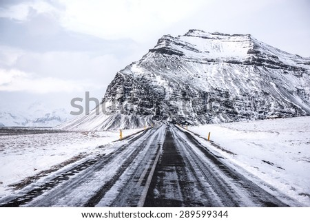 Scenic road and snow covered mountains in Iceland during winter. - stock photo