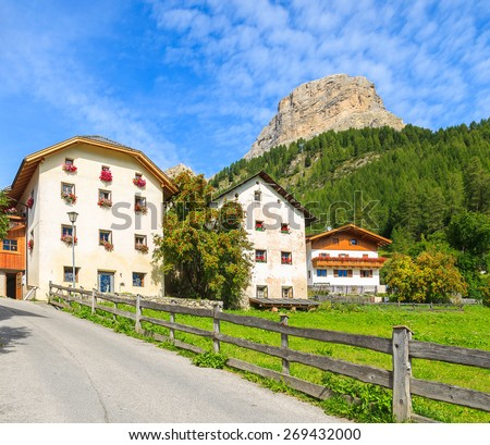 Scenic road and traditional alpine houses in summer landscape of Dolomites Mountains, Italy - stock photo