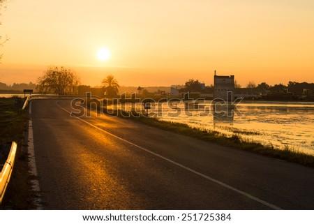 Scenic road crossing endless rice paddies, Albufera, Valencia, Spain - stock photo