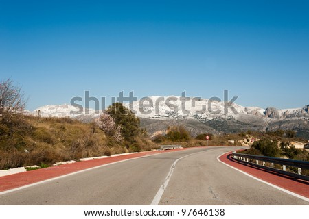Scenic road leading through a winter landscape - stock photo