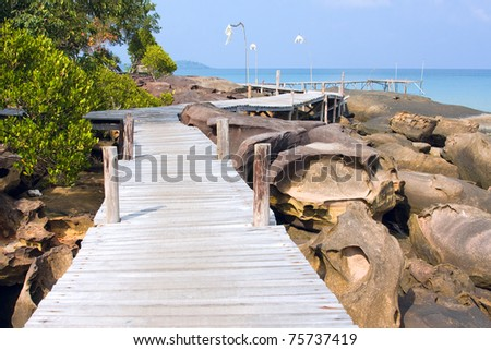Scenic sea coastline of the Koh Kood island in Thailand with wooden path along the rocky shore - stock photo