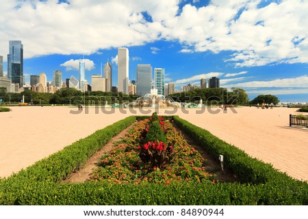 Scenic skyline view of Grant Park in downtown Chicago with tall skyscrapers in the background on a blue sky cloudy day.