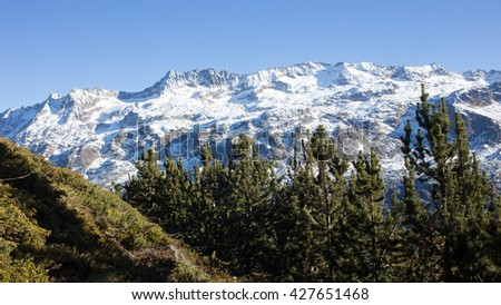 Scenic snow covered mountain peaks in the French Alps with evergreen trees in the foreground - stock photo