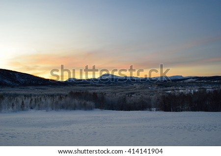 Scenic snowy mountain with vibrant colorful sky and white frost covered forest in the front in the arctic circle - stock photo