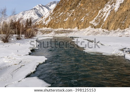 Scenic spring view on the fast mountain river flowing among the shores of ice and snow on background of mountains, trees and blue sky
