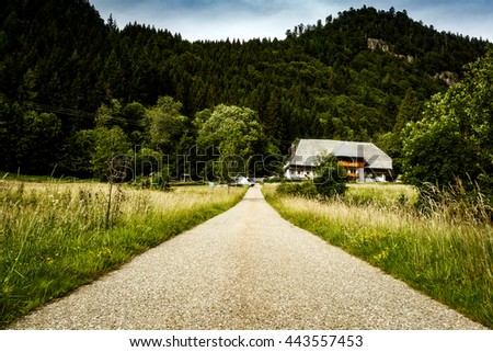 Scenic summer countryside landscape with mountains, fields and old house in Germany.