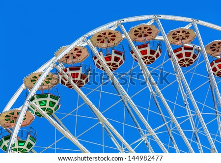 Scenic summer view of color Ferris observation wheel over blue sky in amusement park