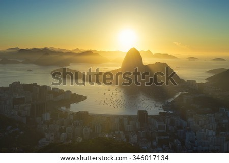 Scenic sunrise in Rio de Janeiro Brazil glows golden over Guanabara Bay with a dramatic backlit silhouette of Sugarloaf Mountain - stock photo