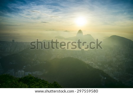 Scenic sunrise in Rio de Janeiro Brazil glows golden over Guanabara Bay with a skyline silhouette of Sugarloaf Mountain - stock photo