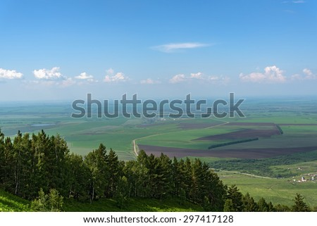 Scenic top view on the town, trees, forest, agricultural fields, farms and villages on the background of blue sky and clouds in summer - stock photo
