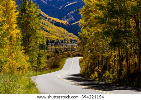 Scenic two lane highway drive in mountain sides filled with fall color of changing Aspen trees and pine trees on sunny afternoon - stock photo