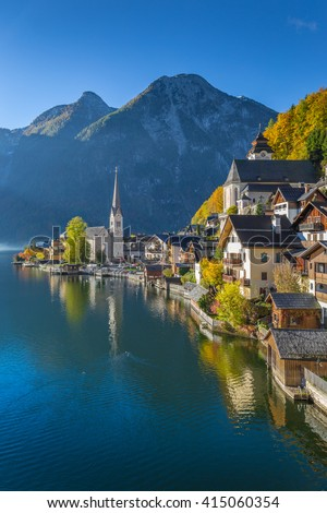 Scenic vertical postcard view of famous historic Hallstatt mountain village with Hallstatter See in the Austrian Alps in beautiful golden morning light at sunrise, region of Salzkammergut, Austria - stock photo