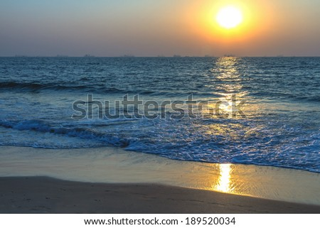 Scenic view from sand beach in Goa to beautiful sunset above the Arabian sea. Sun reflection on sea surface