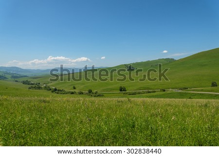 Scenic view from the asphalt road among meadows with wild flowers on the background of mountains and blue sky with clouds - stock photo