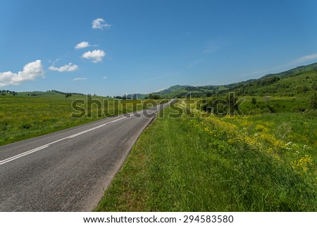 Scenic view from the asphalt road among meadows with yellow flowers on a background of mountains and blue sky with clouds - stock photo
