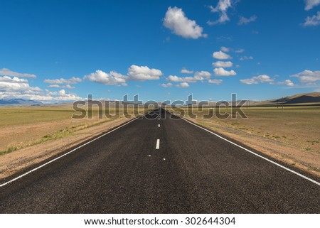 Scenic view from the asphalt road in the steppe on a background of mountains and blue sky with clouds - stock photo