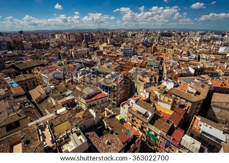 Scenic view from the height of the cathedral in the center of Valencia. Many tile roofs on a background of bright clouds. Typical landscape of Spain - stock photo