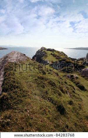 scenic view in kerry ireland of rocks and sea with mountains against a beautiful bright sunny sky - stock photo