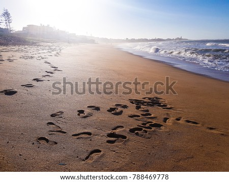 Scenic view of a beach and foot prints on the sand