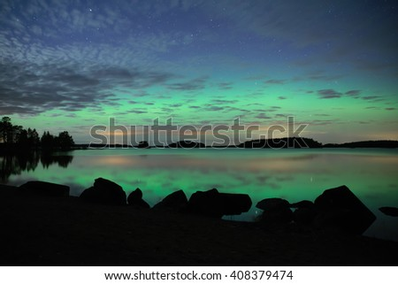 Scenic view of a calm lake with northern lights (Aurora borealis) - stock photo