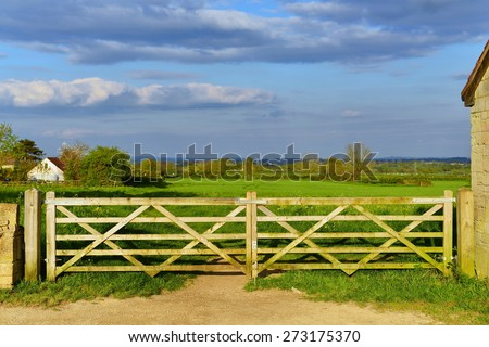 Scenic View of a Farm Gateway and Green Meadow Beyond  - stock photo