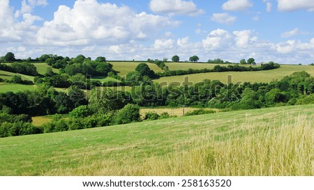 Scenic View of a Green Field and Blue Cloudy Sky in the Avon Valley near Bath in Somerset England - stock photo