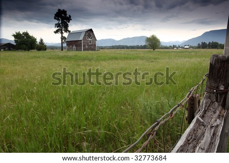 Scenic View of a Montana Farm with mountains in the background. - stock photo