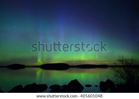 Scenic view of a northern lights over calm lake (Aurora borealis) - stock photo