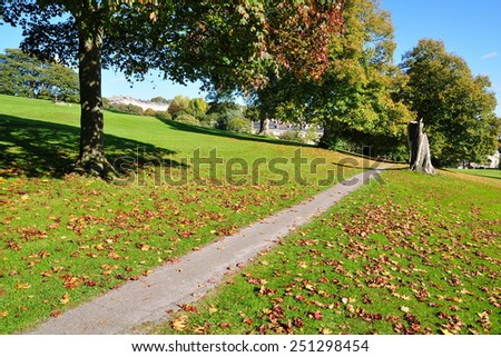 Scenic View of a Path through a Beautiful Leafy Park in Autumn  - stock photo