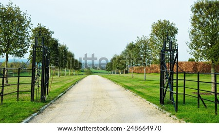 Scenic View of a Tree Lined Driveway through a Beautiful English Country Estate - stock photo