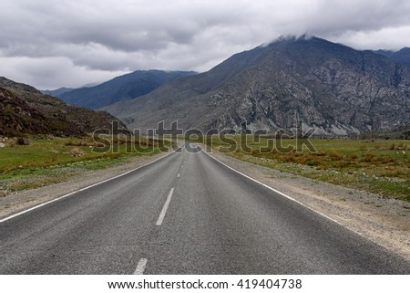 Scenic view of an asphalt road in the mountains on a cloudy day on a background of clouds in spring