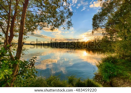 Scenic view of beautiful sunset above the river at summer evening with willow at foreground