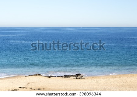 Scenic view of blue green tinted  Ocean Beach, Bunbury, Western Australia on a sunny early morning in autumn  with the tide ebbing away leaving the sandy beach  with waves lapping gently on the shore. - stock photo