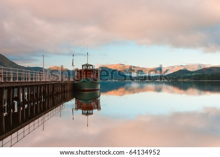 Scenic view of boats moored by wooden pier , Lake District National Park, England. - stock photo