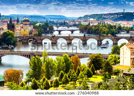 Scenic view of bridges on the Vltava river and of the historical center of Prague: buildings and landmarks of old town with red rooftops and multi-coloured walls. - stock photo