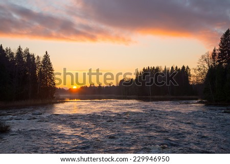 Scenic view of flowing river in sunset - stock photo