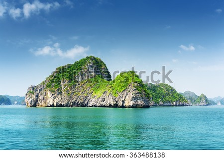 Scenic view of karst rocks-isles and azure water in the Ha Long Bay (Descending Dragon) at the Gulf of Tonkin of the South China Sea, Vietnam. The Halong Bay is a popular tourist destination of Asia. - stock photo