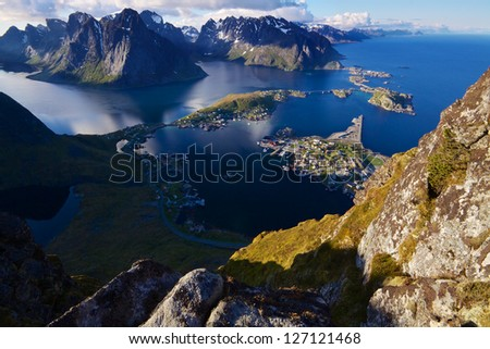 Scenic view of Lofoten islands from top of mountain Reinebringen with picturesque town of Reine and surrounding fjords - stock photo