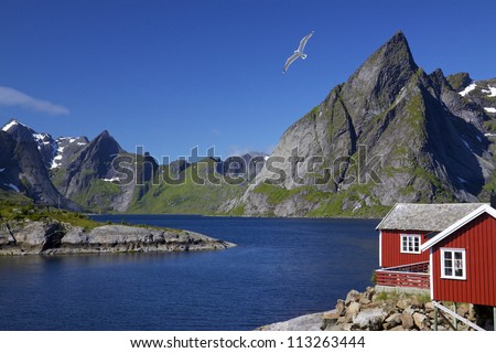 Scenic view of Lofoten islands with typical red fishing hut and towering mountain peaks around deep fjords - stock photo