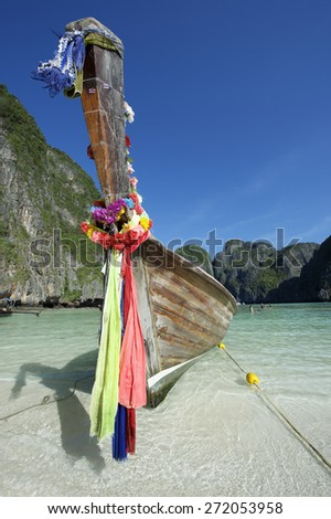 Scenic view of Maya Bay on Koh Phi Phi Leh Island Thailand with traditional Thai wooden longtail boat with decorative sash ribbons  - stock photo