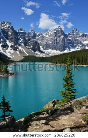 Scenic View of Morraine Lake, Surrounded by Canadian Rockies, Rocks, and Evergreen Trees - stock photo