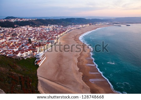 Scenic view of Nazare town and beach from overlooking cliffs during early evening - stock photo