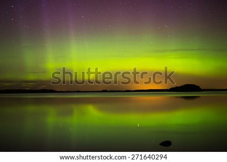 Scenic view of northern lights over calm lake in Sweden (Aurora borealis) - stock photo