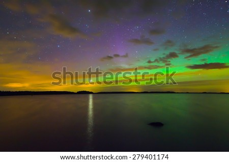 Scenic view of northern lights over frozen lake in Sweden and the star of venus (Aurora borealis) - stock photo