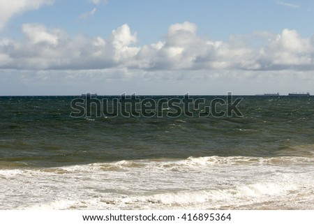 Scenic view of  Ocean Beach Bunbury Western Australia on a stormy  cloudy morning  in late autumn with waves breaking  on the wet sandy shore. - stock photo
