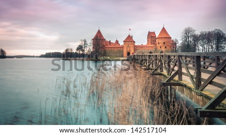 Scenic view of old castle in Trakai, Lithuania with quiet lake and wooden bridge in foreground. Bare trees and gloomy sky in background. Historical places and architecture of Europe. - stock photo