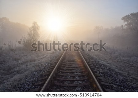 Scenic view of railway going straight ahead through winter field covered by frost to rising sun