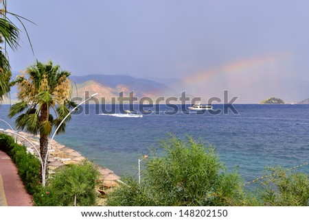 scenic view of sea, stormy sky, rainbow and mountains near Marmaris - stock photo